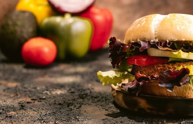 Hamburger di seitan vegan su superficie di legno con verdure. cibo vegano sano