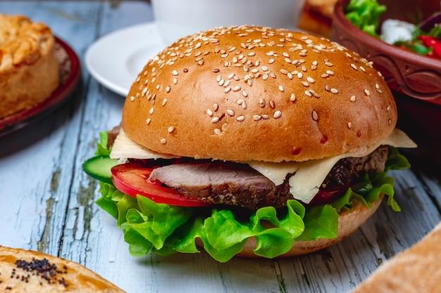 Hamburger di vista laterale con lattuga e pomodoro di formaggio di carne alla griglia tra panini hamburger