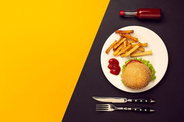 Hamburger di vista superiore con patatine fritte con lo spazio della copia