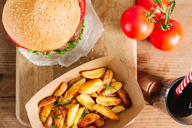 Hamburger e patate fritte del primo piano di vista superiore sul bordo di legno
