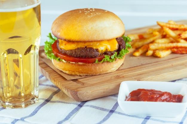 Hamburger e patate fritte sulla tavola di legno