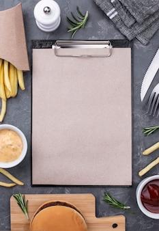 Hamburger e patatine fritte deliziosi con la lavagna per appunti accanto