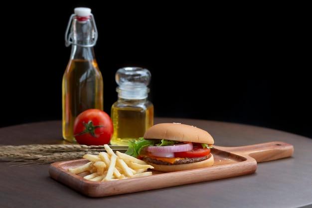 Hamburger e patatine fritte fatti in casa su sfondo nero.