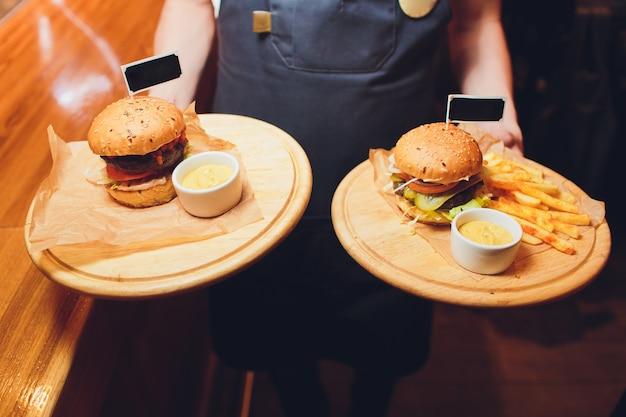 Hamburger e patatine fritte sul vassoio di legno.