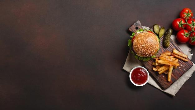 Hamburger fatti in casa con ingredienti di manzo, pomodori, lattuga, formaggio, cipolla, cetrioli e patatine fritte sul tagliere e sfondo arrugginito