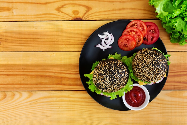 Hamburger fatto a mano su superficie scura. hamburger nero delizioso