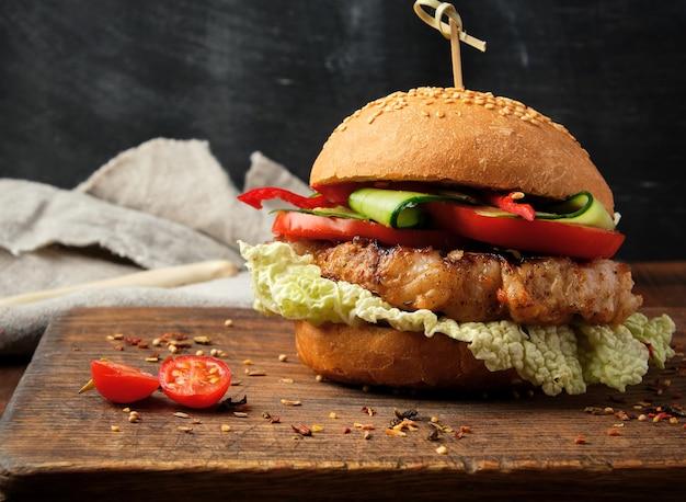 Hamburger fatto in casa con bistecca fritta di maiale, pomodori rossi, panino rotondo fresco con semi di sesamo