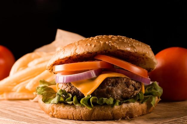 Hamburger fatto in casa con carne di manzo, cipolla, pomodoro, lattuga e formaggio. fine fresca dell'hamburger su sulla tavola rustica di legno con le patate fritte, la birra e le patatine fritte. cheeseburger.