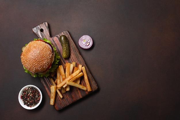 Hamburger fatto in casa con ingredienti di manzo, pomodori, lattuga, formaggio, cipolla, cetrioli e patatine fritte