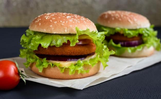 Hamburger fresco con formaggio, cotoletta e pomodoro su sfondo nero