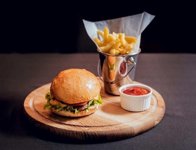Hamburger grande e gustoso con fuochi sulla scrivania in legno.