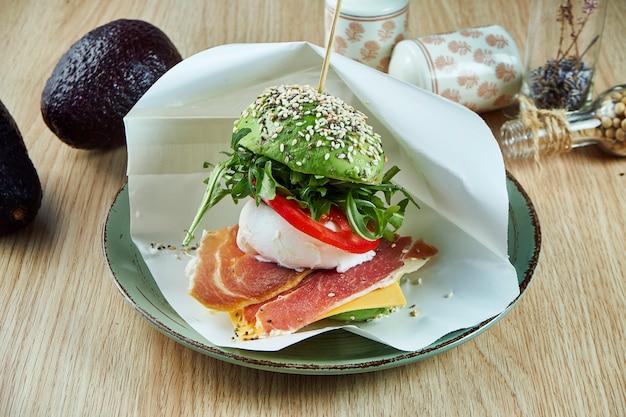 Hamburger insolito fatto da metà di avocado con formaggio, uovo in camicia, jamon e rucola. cibo di strada gustoso e salutare.