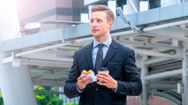 Hamburger mangiatore di uomini bello della prima colazione mangiatrice di uomini di affari e tazza di caffè bevente