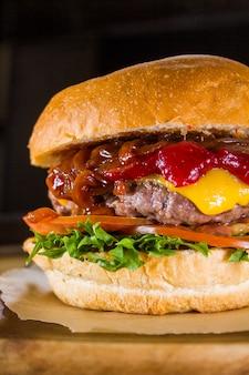 Hamburger mezzo con il primo piano del manzo, delle verdure, del formaggio e della salsa sul nero.