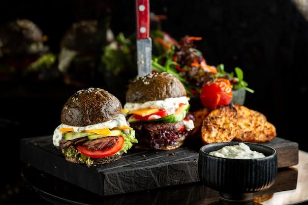 Hamburger nero classico di carne con salsa