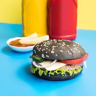 Hamburger nero con bottiglie di ketchup e senape