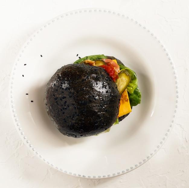 Hamburger nero con carne di manzo su sfondo nero