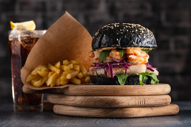 Hamburger nero con pesce e gamberi, fishburger con gamberi e patatine fritte