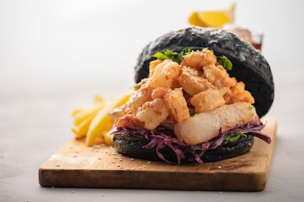 Hamburger nero con pesce e gamberi, fishburger con gamberi su sfondo chiaro