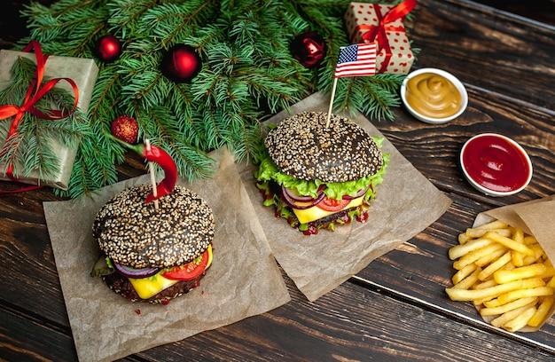 Hamburger nero di due natali con il nero americano, la lattuga, il pomodoro e le patate fritte. fondo in legno