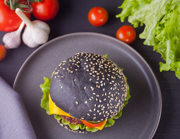 Hamburger nero fatto in casa con cotoletta e verdure sul piatto
