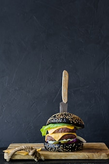 Hamburger nero su un tagliere di legno. sfondo con copyspace