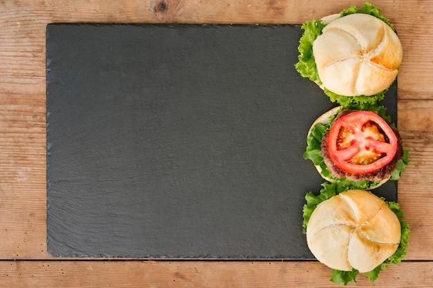 Hamburger piatto-lay su ardesia con copyspace