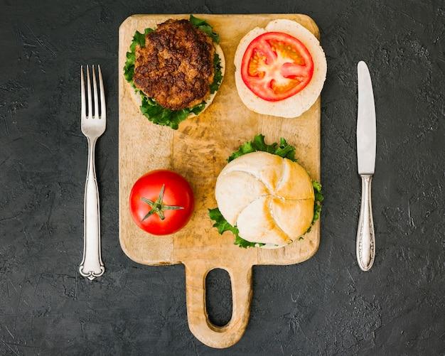 Hamburger piatto sul bordo di legno con posate