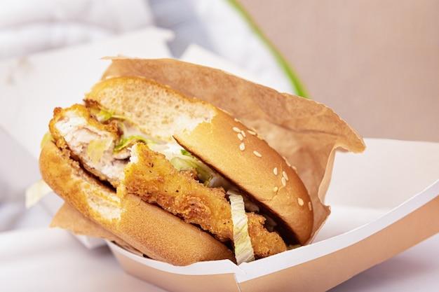 Hamburger pungente in una scatola di cartone, fine in su.