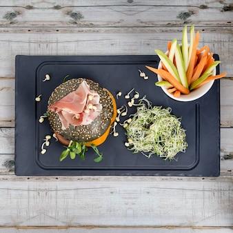 Hamburger sano con hamon, pomodori, micro verdi e panini integrali neri, bastoncini di verdure sul bordo di ardesia nera sul tavolo di legno. mangiare pulito, dieta, concetto di cibo disintossicante.