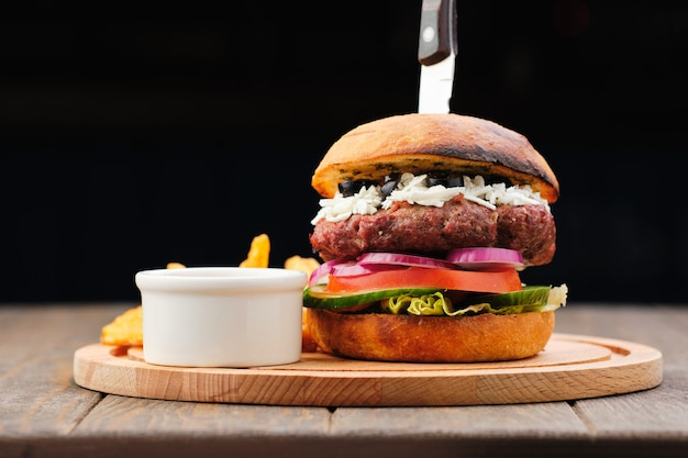 Hamburger saporito casalingo e fresco sul bordo di legno