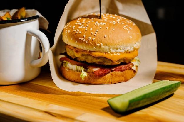 Hamburger saporito delizioso con lattuga, formaggio, cipolla e pomodoro su una plancia di legno rustica su un fondo nero