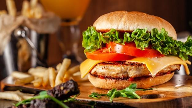 Hamburger succoso con tortino di carne, pomodori, formaggio cheddar, lattuga e panino fatto in casa.