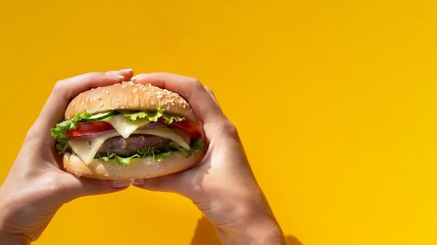 Hamburger tenuto di fronte a sfondo giallo