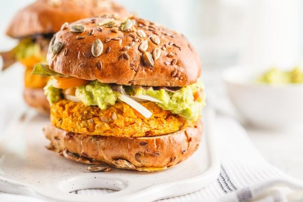 Hamburger vegan della patata dolce (o zucca) su fondo bianco. hamburger di verdure, avocado, verdure e focacce.