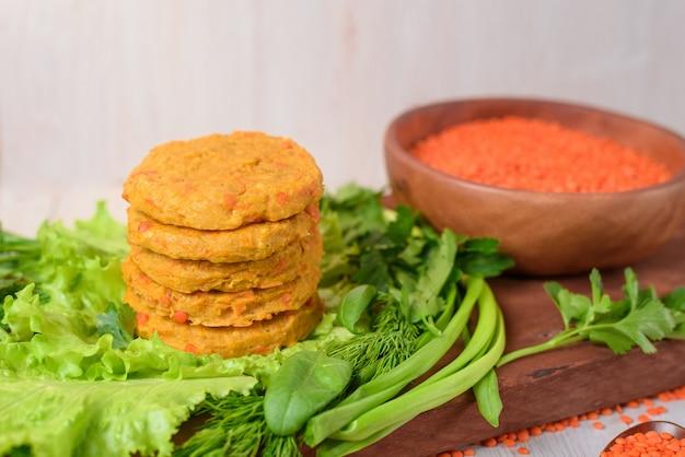 Hamburger vegani della lenticchia e della carota in un piatto di legno con insalata verde su una luce
