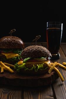 Hamburger vegetariano con patatine fritte e bevande sul tavolo di legno