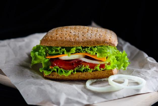 Hamburger vegetariano su carta su una superficie nera