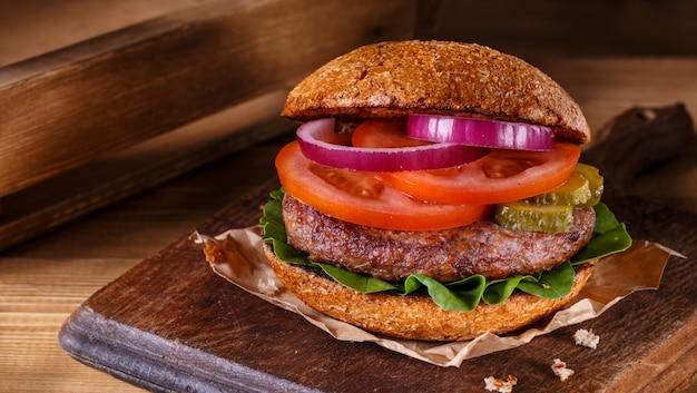 Hamburger vicino su un tagliere su fondo di legno.