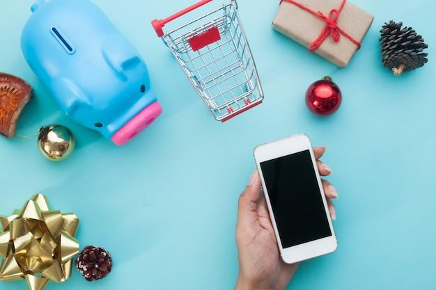 Hand holdin smartphone con decorazioni natalizie. natale mock up modello per il concetto di shopping online. vista dall'alto