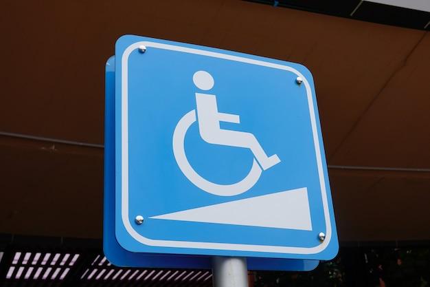 Handicap blu al parcheggio auto segno all'aperto per disabili e sedia a rotelle.