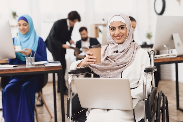 Handicappato lady con laptop lavora in ufficio.