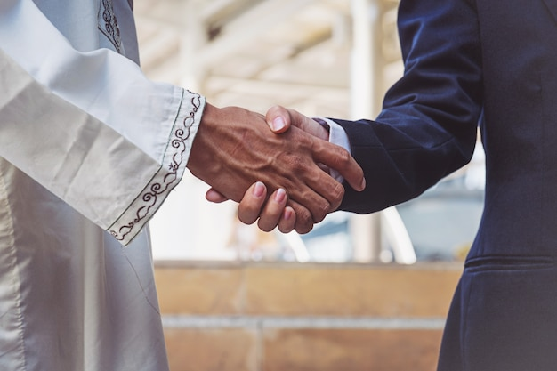 Handshake arabo dell'impiegato degli uomini d'affari sul cantiere