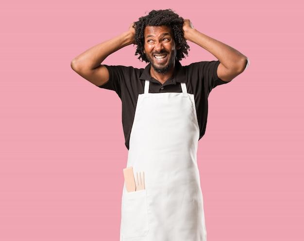 Handsome african american baker pazzo e disperato, urlando fuori controllo