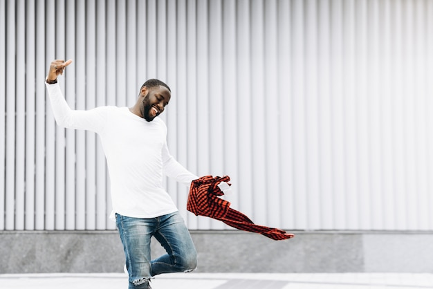Handsome afro americano che indossa abiti casual che saltano e ballano con grunge background di parete di cemento.