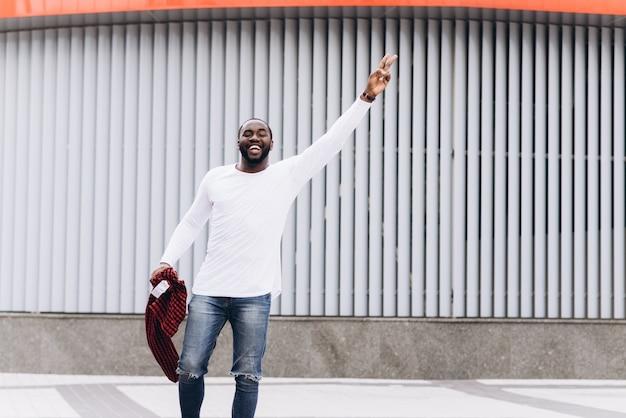 Handsome afro americano indossa abiti casual ballo con sfondo grunge muro di cemento.