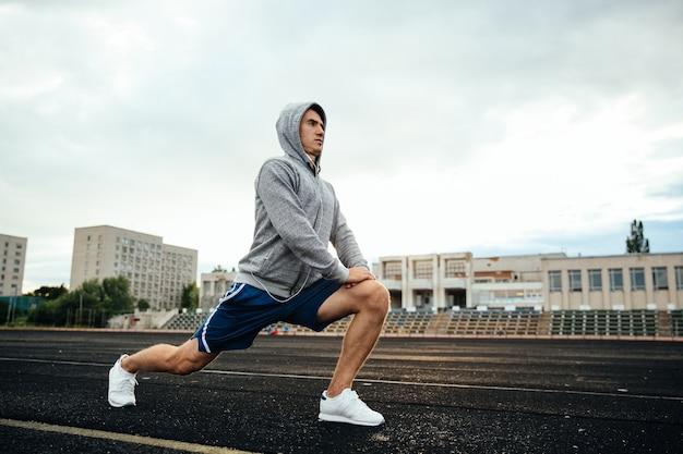 Handsome giovane sportivo facendo affondi, esercizi, ascoltando musica, allo stadio.