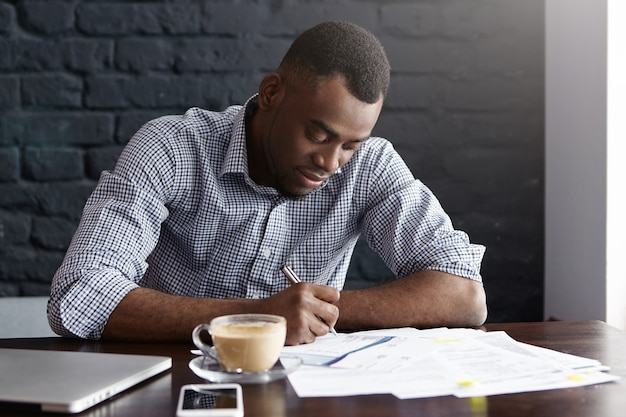 Handsome giovane studente maschio afro-americano in camicia alla base di informazioni importanti in carta