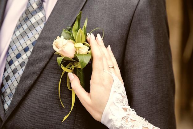 Hang di una sposa che aggiusta il boutonniere sulla giacca degli sposi