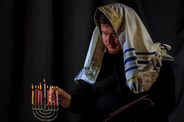 Hanukkah, una celebrazione ebraica. candele accese nella menorah, uomo sullo sfondo.